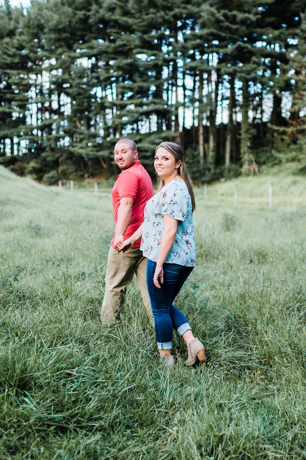 couple walking through field together during engagement session in westminster maryland