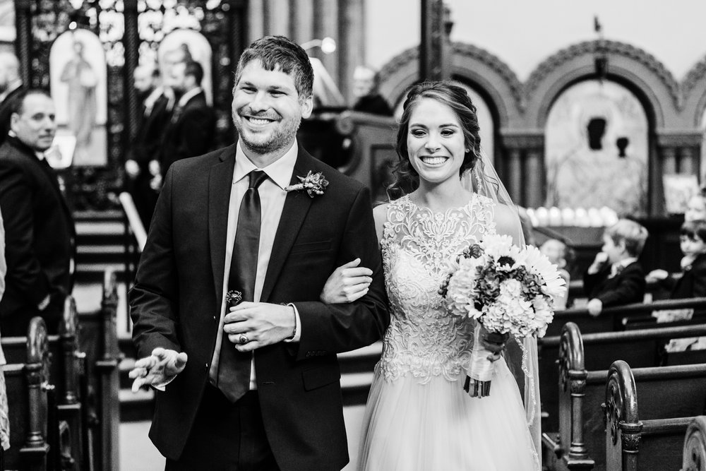 bride and groom smiling coming down the aisle - baltimore greek orthodox wedding - maryland wedding photographer - husband and wife team