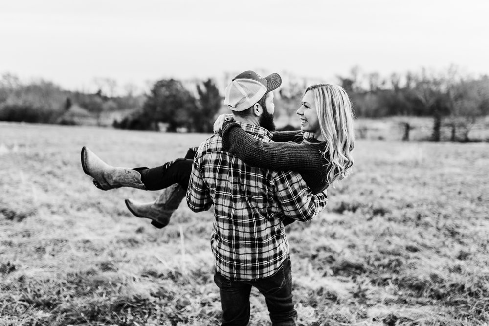 couple in a field laughing - MD wedding photo and video