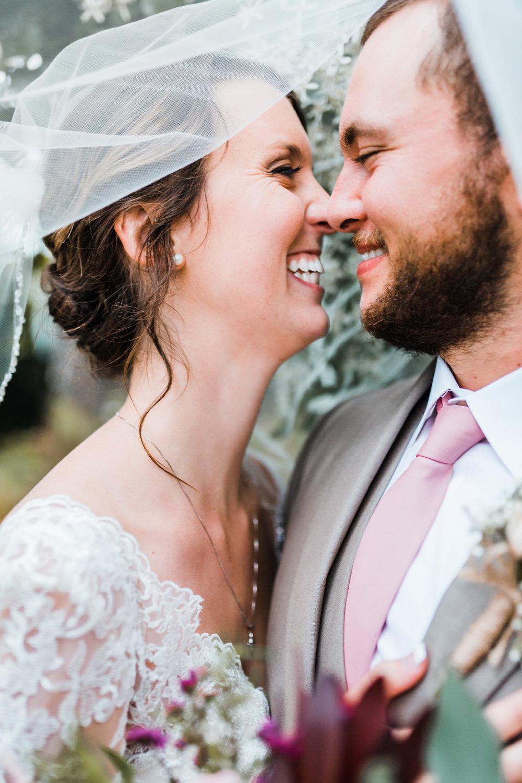 bride and groom together under veil