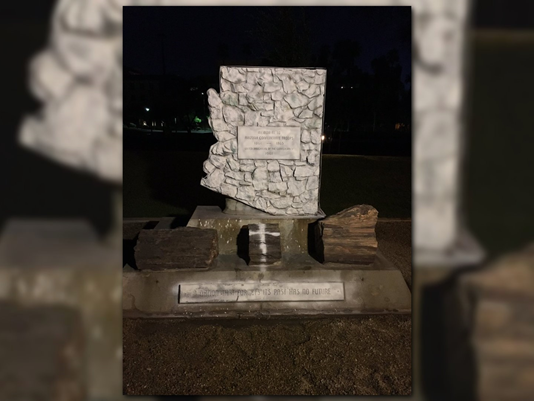 White spray paint covers the stone memorial and placard. A crudely-made cross was added as well.