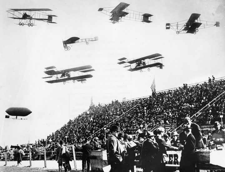 Composite photograph of early-model biplanes, a monoplane, and a dirigible passing by bleachers filled with spectators at the 1910 Dominguez Field Air Meet. Source:  Water & Power Associates