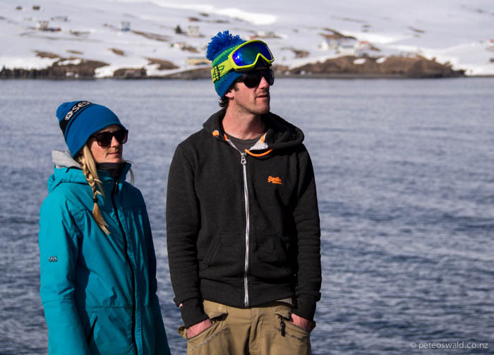 Soph and Will stand in front of the tiny fishing village of Ólafsfjörður while they look for skinning access up the next mountain