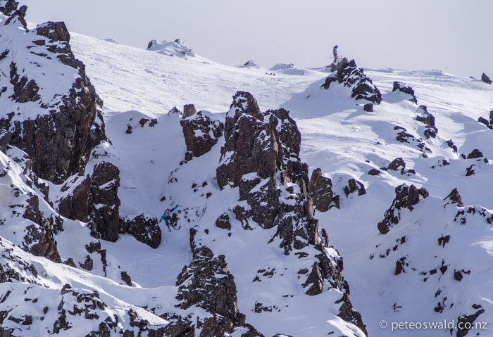 Taylor Rapley airs into a chute on her way to winning the woman's ski category, Ross waits to drop from the ridge