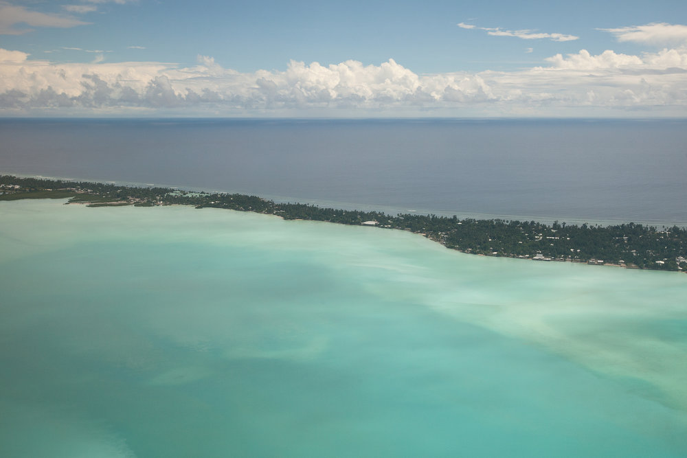 An aerial view of Tarawa, the capital of Kiribati, at high tide. The island lies only a couple of metres above sea level, and at high tide almost disappears into the ocean. More than half of Kiribati's 100,000 people live in South Tarawa in an area of just over 10  km2, giving it a population density comparable to London.