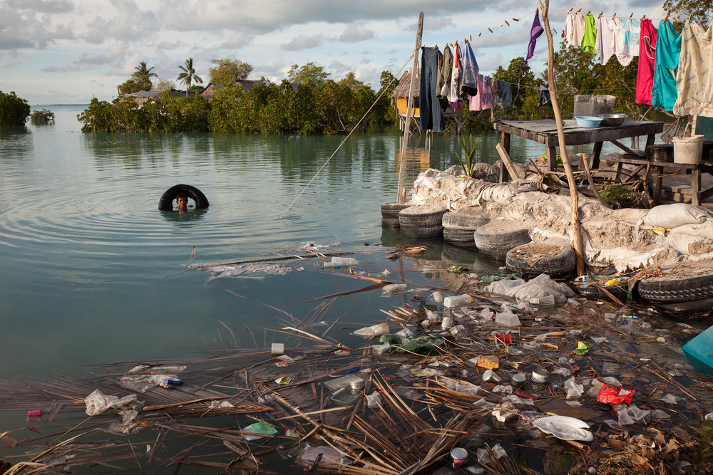 A boy swims in the lagoon next to his house in Temwaiku that is heavily polluted with rubbish brought in by the tide each day.