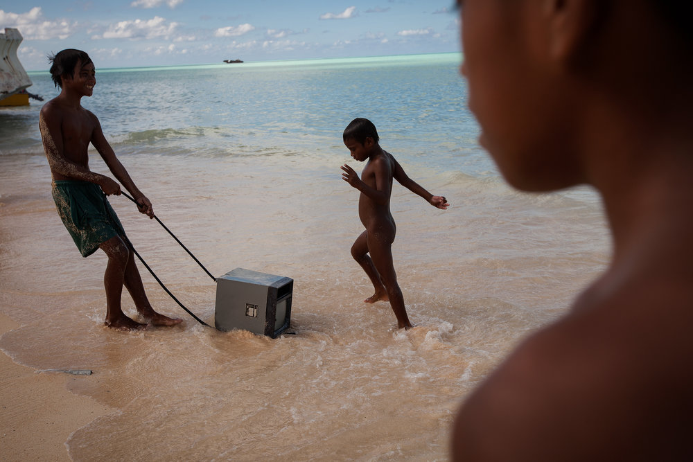 Children play with an old monitor that has washed up on the shore at Red Beach in South Tarawa. Every day, the hide tide brings in all manner of rubbish. With virtually no hard (or soft) waste management in Tarawa, the island suffers from a serious pollution problem.