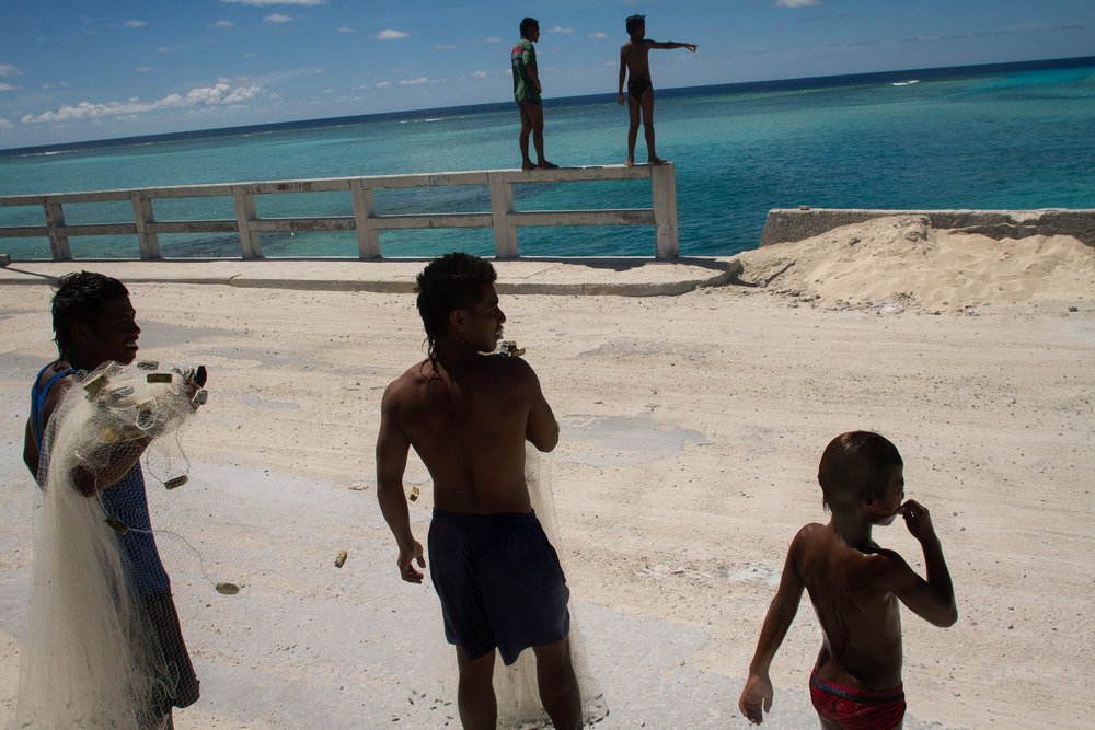 Young men spot schools of fish from a bridge near Betio in Tarawa. Fishing and the ocean are intrinsic to the way of life of young men in Kiribati.