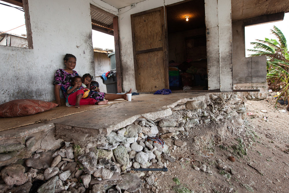 Jondrick Joash, 54, and her granddaughters Nola and Judy live in their half demolished house in Utidrikan, Majuro. The front rooms and kitchen were washed away by waves in February 2014, leaving just the front door, one tiny bedroom and a narrow strip of concrete that falls away to the eroded shore below. Eleven people live in the cramped ruin.