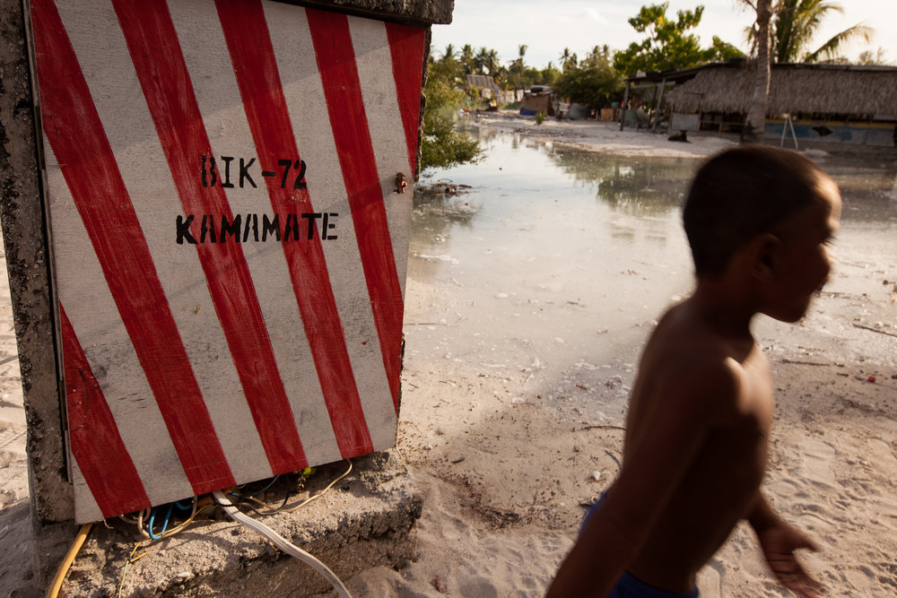 A young boy walks in front of a power box in Golden Beach as the tide fills in toward the wires. Last year a nearby box exploded when the water made contact with the wires.
