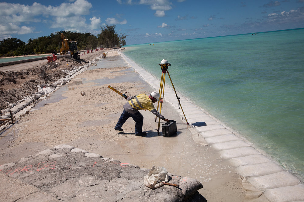 A worker removes equipment away from the incoming tide. The maintenance to this piece of road is interrupted every day with the high tide as the water comes up over the site.