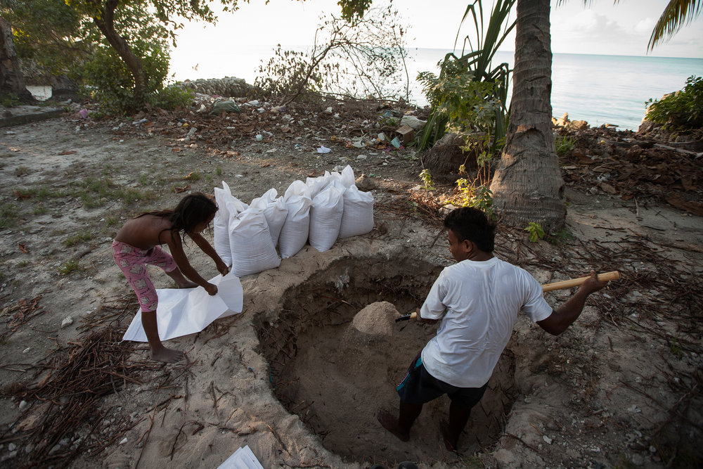 Iaonnatu Tikabenca, 26, and his cousin Aroua Kuratake, 8, fill bags with sand from the lagoon side of South Tarawa that will be used by their uncle to build a seawall on the ocean side of the atoll.
