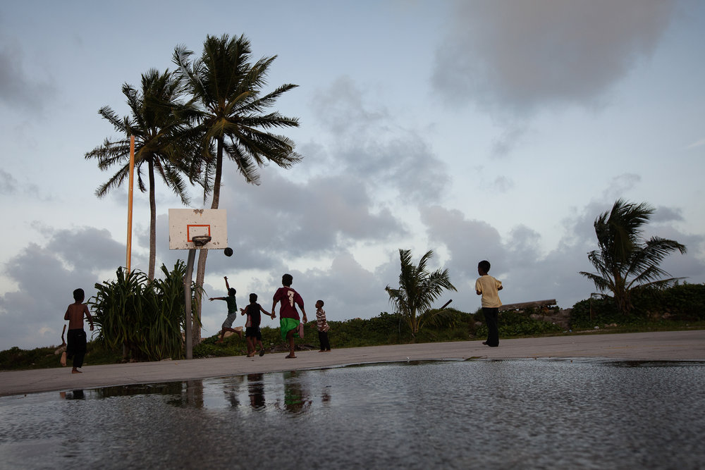Young boys play basketball in Majuro after a storm. Basketball is the most popular sport in the Marshall Islands, and many children want to grow up and play in the United States. Marshallese are free to live and work in the US under a Compact of Free Association, making that the most likely destination should they have to leave their islands.