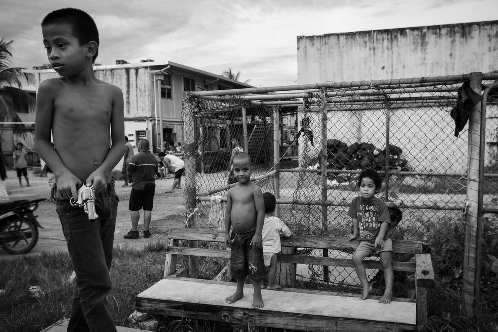 A young Nauruan boy plays with a toy gun in Location Block.