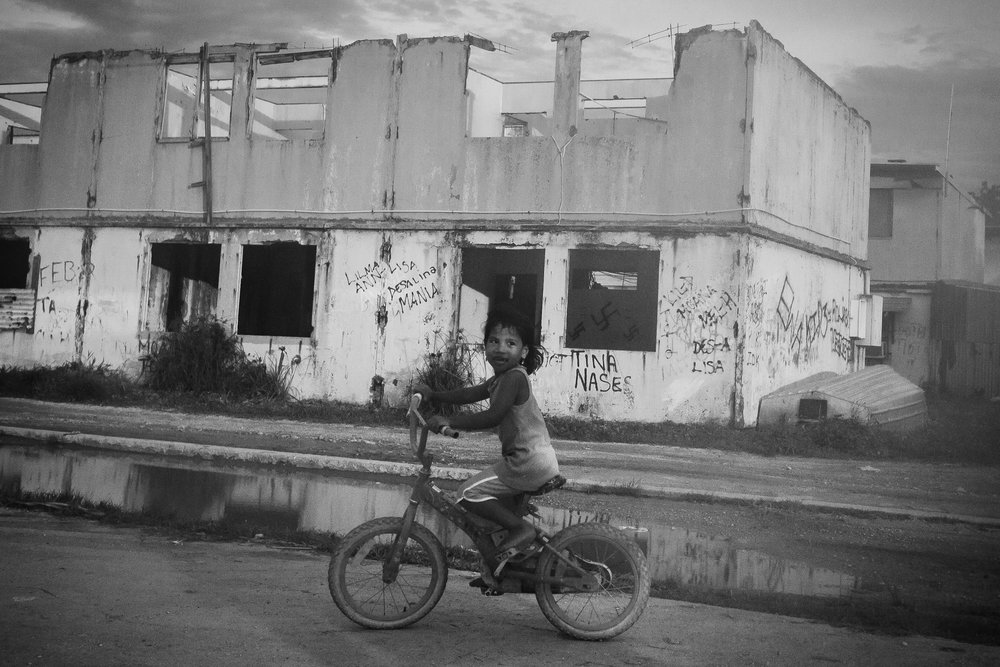 A young girl rides past abandoned houses in Location Block.