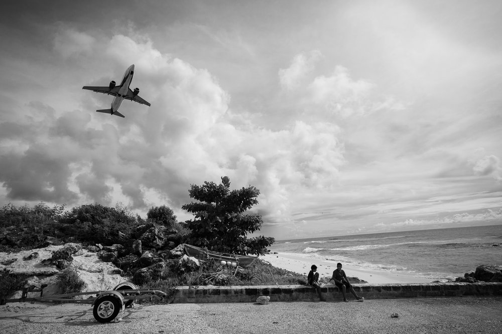 Two local Nauruan boys watch a plane take off. When a plane takes off or lands on Nauru, you can see it from anywhere on the island, and they quite often fly directly over the detention centres, teasingly in full view of the refugees below.