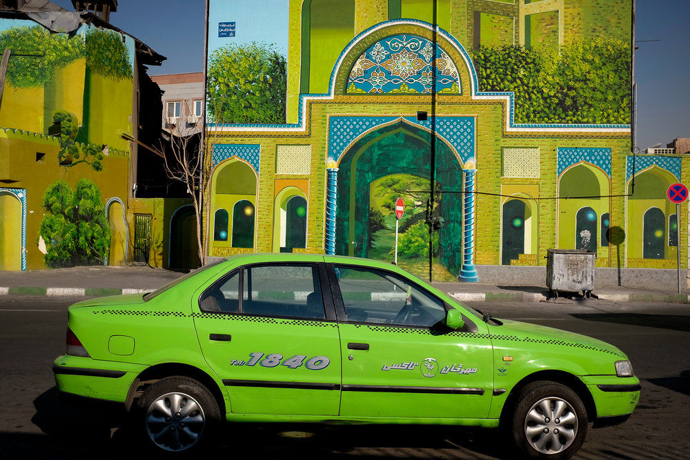 A taxi waits for a ride in Central Tehran in front of a colourful mural. Buildings in Tehran are often covered in colourful, idyllic scenes that seem quite foreign to the crowded, polluted metropolis that is modern Tehran.