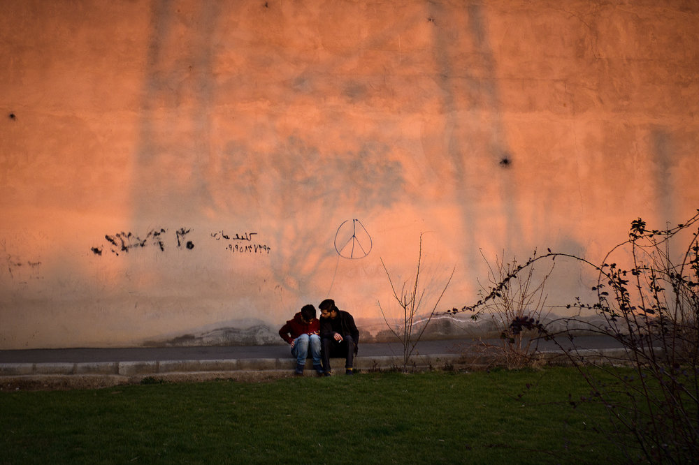 Two young men check their Facebook under graffiti in Western Tehran. Facebook is banned in Iran, but most young people freely access the site through the use of proxy defying software like Tor.