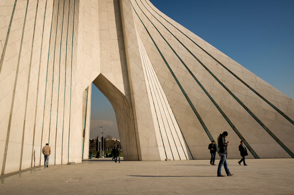 Men make their way around the gateway to Tehran, the Azadi Tower. Hossein Amanat, the architect of Azadi Tower, which translates to 'Freedom Tower', had to flee Iran eight years after the completion of his masterpiece because he was a member of the persecuted minority Baha'i.
