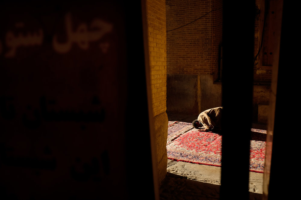 A man prays towards the setting sun in a mosque in Shiraz.