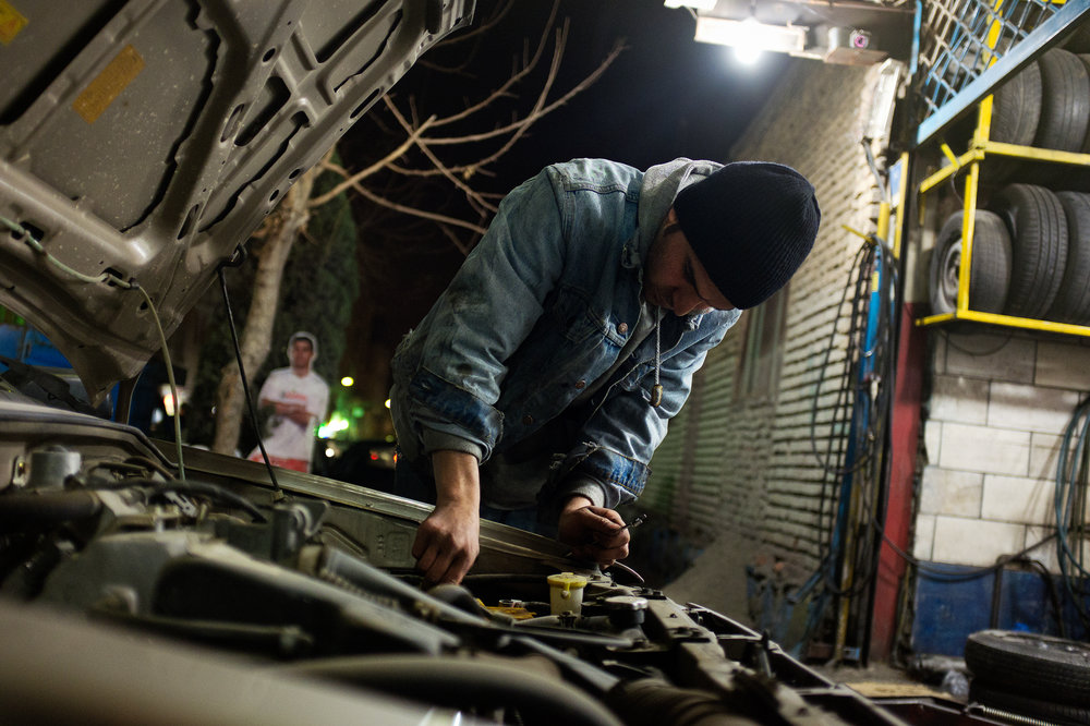 A mechanic tinkers late into the night inside an old Saipa in Tehran. It can be incredibly difficult to find work in Iran, and when employment is found the wages are very low, so people work long hours to make as much money as they can.
