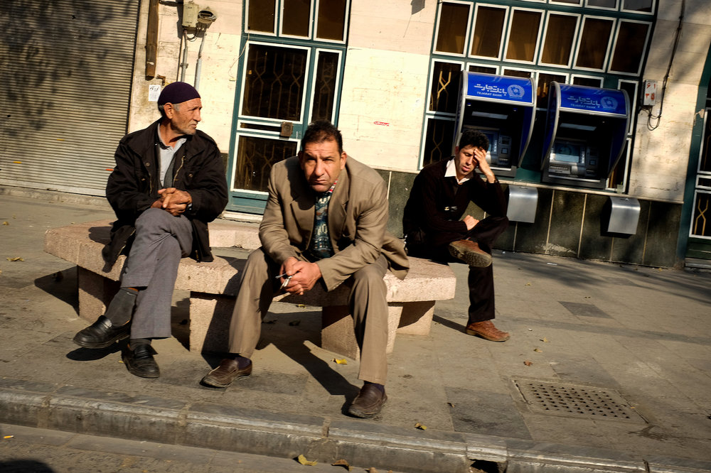 Three men wait for a bus in Tehran. Public buses are still segregated between men and women in Tehran.