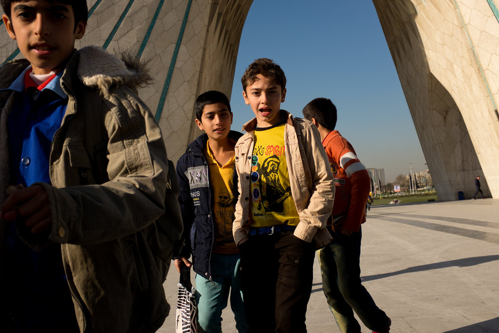 Children on an excursion run underneath the Azadi Tower in Tehran.