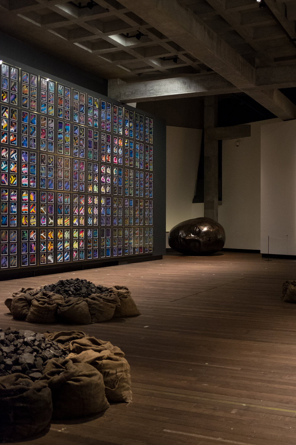 Left: 'Snake', 1970 to 1972  Sir Sidney Nolan (1917, Melbourne, Australia; died 1992, London, England) Mixed media on paper, 1620 sheets  Floor:   'Untitled', 2002  Jannis Kounellis (1936, Piraeus, Greece; lives and works in Rome, Italy) Jute coffee bags, coal  Right:  Artifact, 2010  Gregory Barsamian (Chicago, Illinois, USA, 1953) Steel, foam rubber, paper, acrylic resin