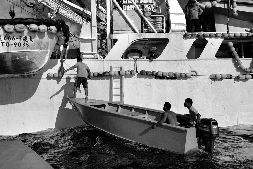 Local men from Tarawa dock next to a purse seiner to receive a smaller tuna. The arrival of the global fishing industry on their doorstep has completely changed the fishing habits of the I-Kiribati.