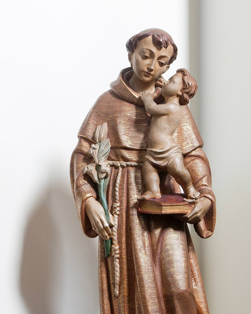 St. Anthony of Padua - This statue is one of three given in memory of Diana Mary Lewis.  It depicts St. Antony of Padua, a Franciscan friar and notable preacher.  After a period as Provincial of the Order, Antony retired to Padua, to a life devoted to preaching. Revered since the 17th century as the finder of lost things, there is  a legend associated with his preaching to the fishes.  He is also known for his devotion to the poor.  Canonised in1232 by Pope Gregory IX, he was declared a Doctor of the Church by Pope Pius XII in 1946, and his feast day is June 13th.