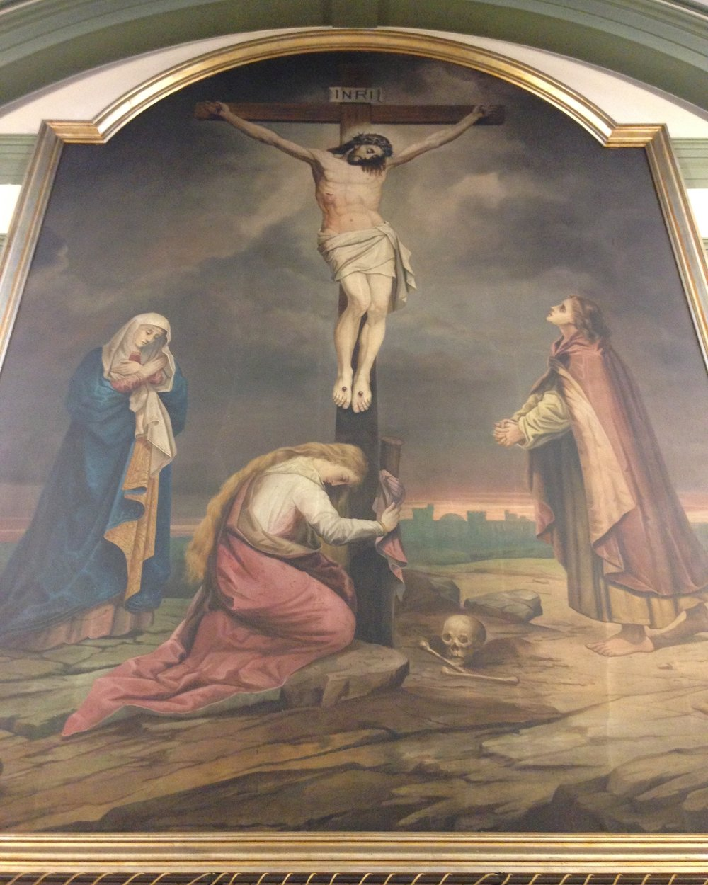 "The Crucifixion - This mural, painted by the brother of Canon Keens (the ""church builder""), originally covered the whole of the central portion of the East wall, but was reduced in size and enclosed in its ""frame"" during the time of Canon de Zulueta as Rector.  As is traditional, it depicts Our Lady, St. Mary Magdalene and St. John, the beloved disciple, at the foot of the cross."