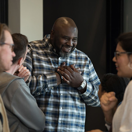 Edrin Williams, associate pastor, talks with people during a Sunday morning worship service at Sanctuary Covenant Church. (Credit: Angela Jimenez for MPR News)