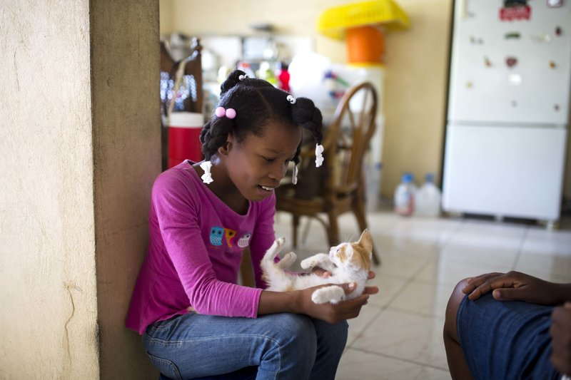 Franchina 11, plays with a cat at her foster home in Port-au-Prince, Haiti. (AP Photo/Dieu Nalio Chery)