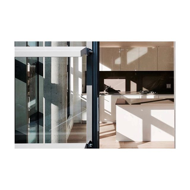 Floor to ceiling glass walls with fins on the facade that cast interesting shadows on this minimal kitchen #shadows #facade #kitchen #light #cast