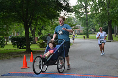 """Andrea Sancho-Baker and her stepdaughter running in the """"Sweat it Out 5k"""" (a run to honor those with Hypohydriatic Ectodermal Dysplasia). The two """"love doing races together and had a blast!"""""""