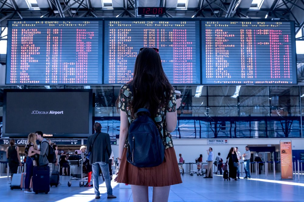 Girl looking at flight screens at the airport. Photo by JESHOOTS-com on Pixabay