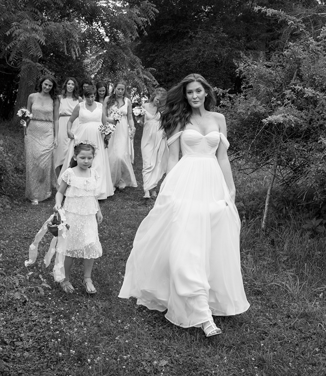 hudson-valley-farm-weddings-pioneer-farm-weddings-warwick-ny-bride-walking-with-bridal-party-black-and-white.png
