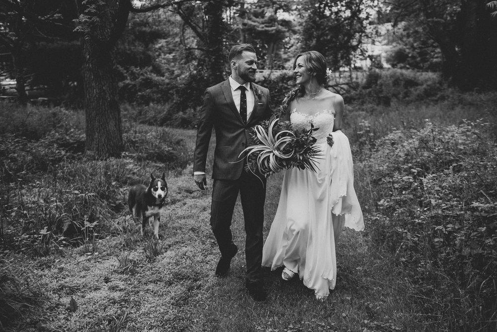 hudson-valley-farm-weddings-pioneer-farm-weddings-warwick-ny-newlyweds-walking-on-trail-with-dog.jpg