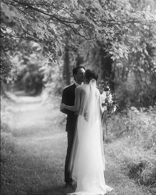 hudson-valley-farm-weddings-pioneer-farm-weddings-warwick-ny-husband-and-wife-kiss-under-tree-black-and-white.png