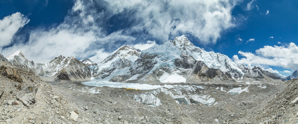 Everest basecamp (yellow/orange tents), Khumbu Glacier (behind basecamp), and Khumbu Icefall (above glacier). Nuptse in the background 7,861 m (25,791 ft) in the center-right. Everest slightly hidden behind the clouds in the middle-back.