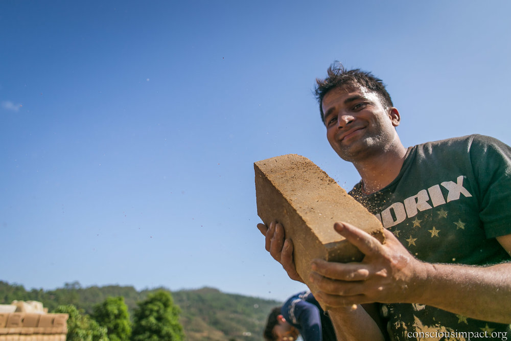 Udav catching one of hundreds of bricks from a volunteer as we load the truck for his home.