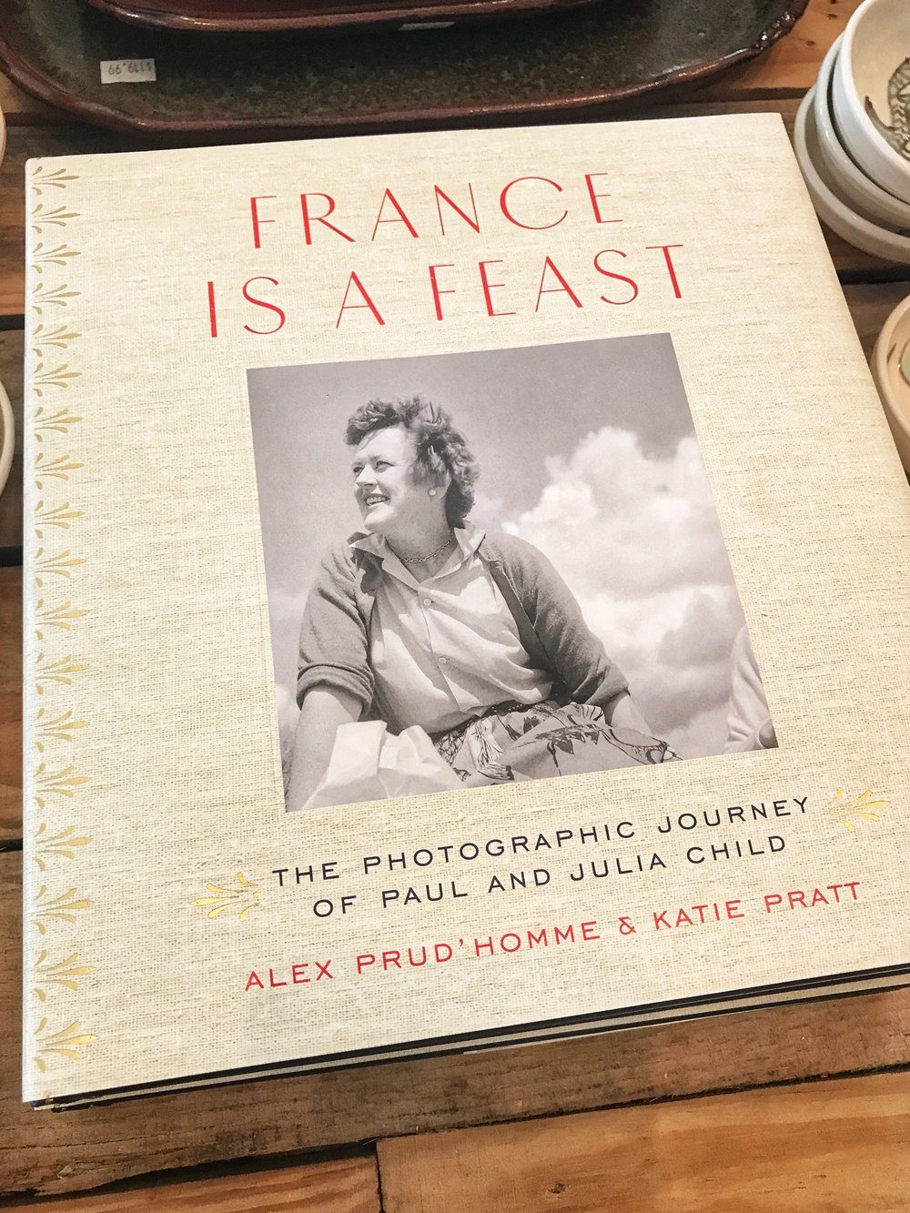 """Thoroughly delicious… Comprised of 225 black-and-white photographs by Paul Child, the husband of Julia Child, taken during the couple's time in France beginning in 1948, this intimate photo album delivers mesmerizing visual addenda to Julia Child's memoir, My Life in France. Zeroing in on postwar Paris, the book covers the couple's early years in France and yields a unique perspective on postwar Europe as well as on the backstory of the woman whose name is synonymous with French cuisine in 20th-century America. The collection includes photos of Julia's days at the Cordon Bleu with fellow chefs, as well as snapshots of her at work amid pots and pans in the tiny kitchen of the couple's Paris apartment. In other photos, Paul plays with shadows and angles while shooting the streets of Paris or the fields of the French countryside. There are also the more everyday traveler's shots featuring a leggy Julia that illuminate the love story between the photographer and his muse."" - Publishers Weekly"