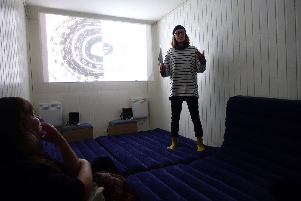 Kurator Becca Clark introduserer filmene  All the time in the world  (2005) av Semiconductor og  Two years at sea  (2011) av Ben Rivers.