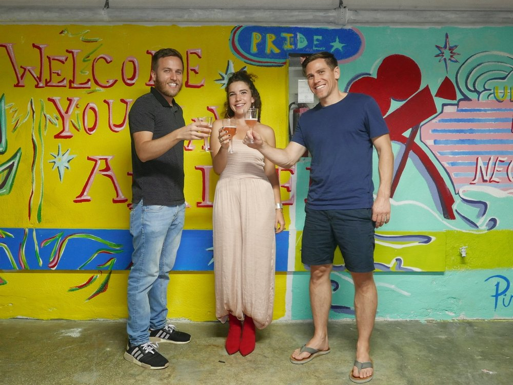 Nick Fenmore, Kate, and Nick Halaris toast the completion of Kate's mural.