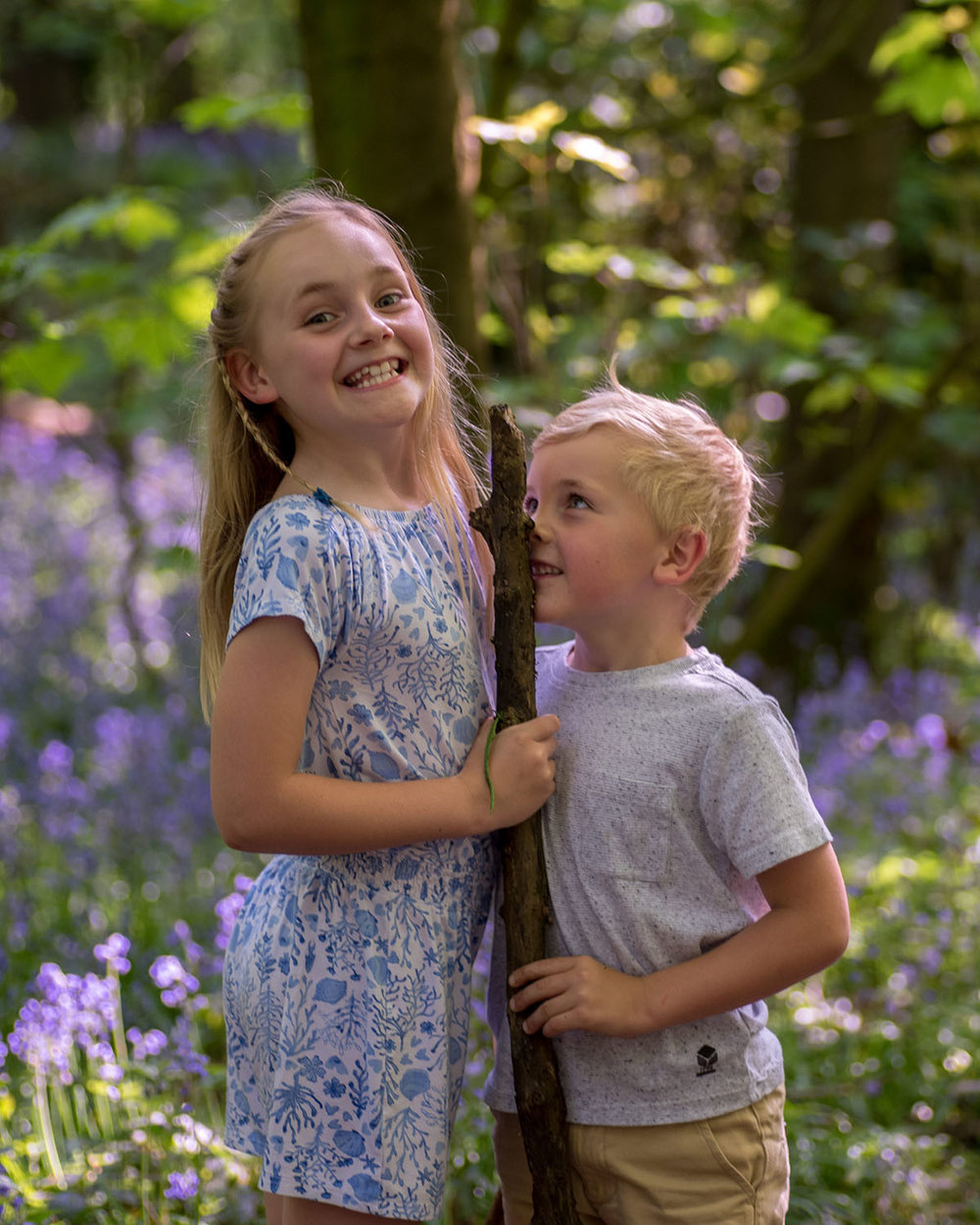 A family photo shoot in Oldmoor woods, Nottinghamshire. Here the kids are playing with a stick. Nottingham family photography