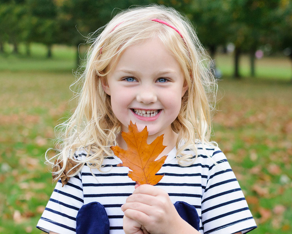 Happy fun-loving girl enjoying a family photography session in autumn
