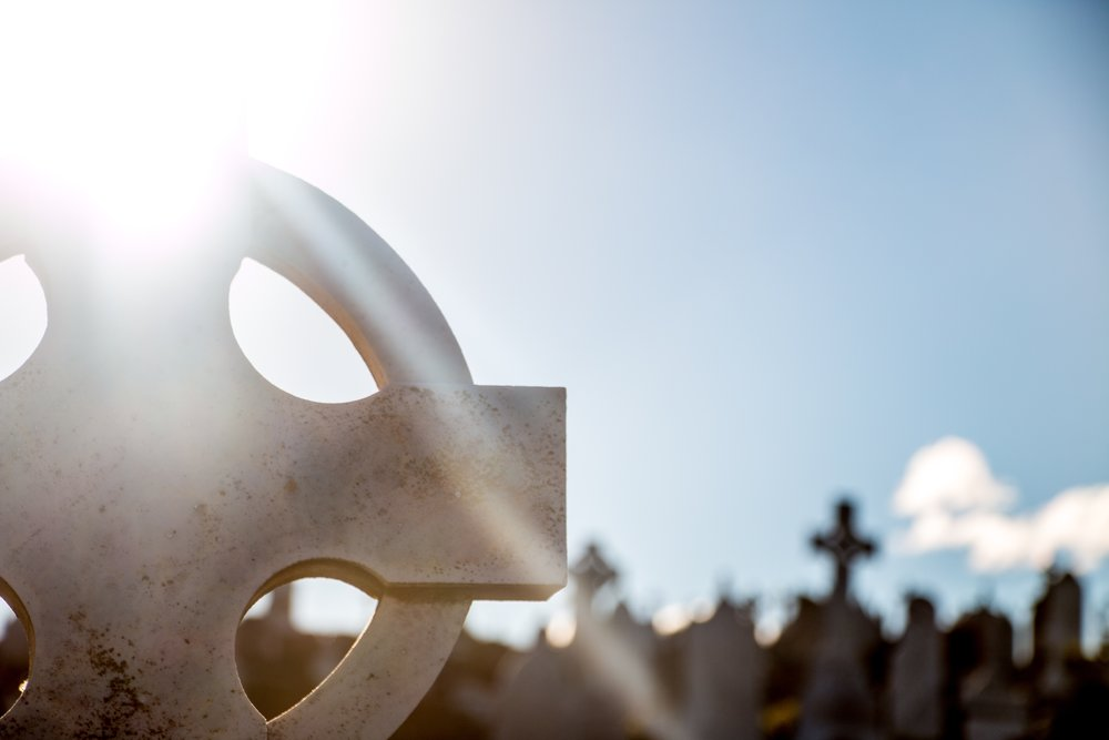 A cemetery with the sun shining through the cross on a headstone, represents a place of difficulty, sadness, and grief