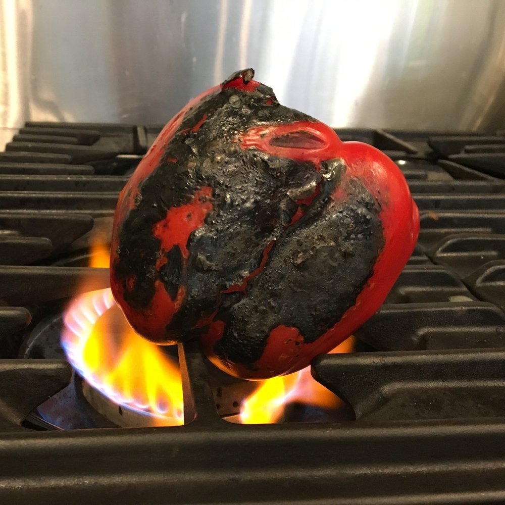 Stove or grill: Leave the pepper over the flame until the skin is completely charred. Rotate and char on each side. Don't forget the top and the bottom of the pepper as well.  Oven: If you are roasting in the oven, simply rotate the pepper a few times. The pepper is done when skin is lightly charred and the fruit is squishy to touch. For solid vegetables like squash and eggplant, it is done when the skin is tough and rubbery and the vegetable gives in to a light squeeze or a fork inserts easily into the tender flesh.