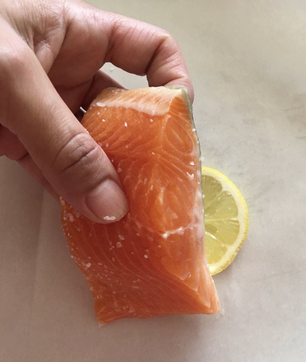 4. Place a slice of citrus on each piece of parchment. Lay the fish fillet on top.