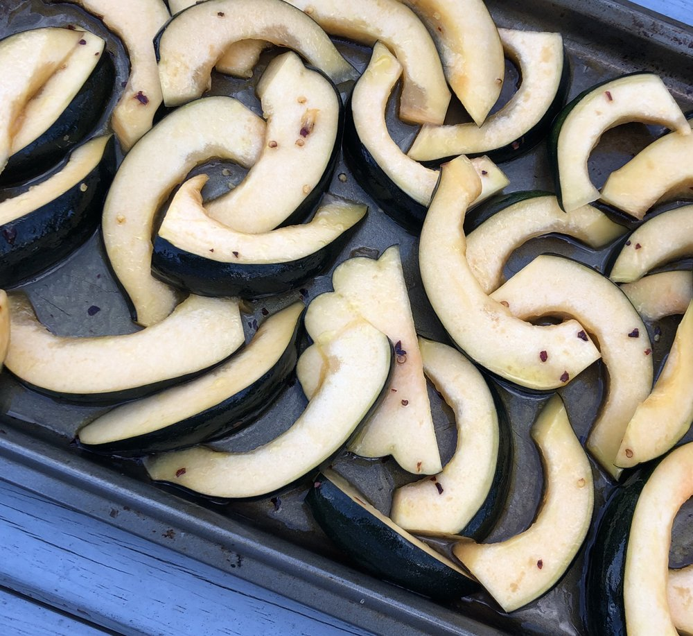 Acorn squash cut into crescent shaped slices and tossed in chili maple glaze before roasting.
